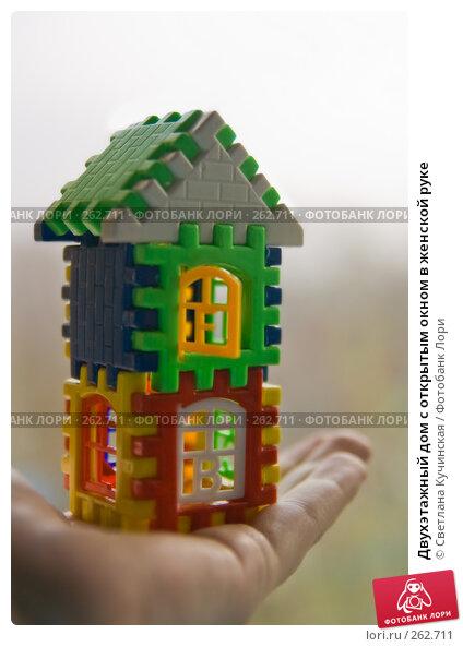 Двухэтажный дом с открытым окном в женской руке, фото № 262711, снято 22 июля 2017 г. (c) Светлана Кучинская / Фотобанк Лори