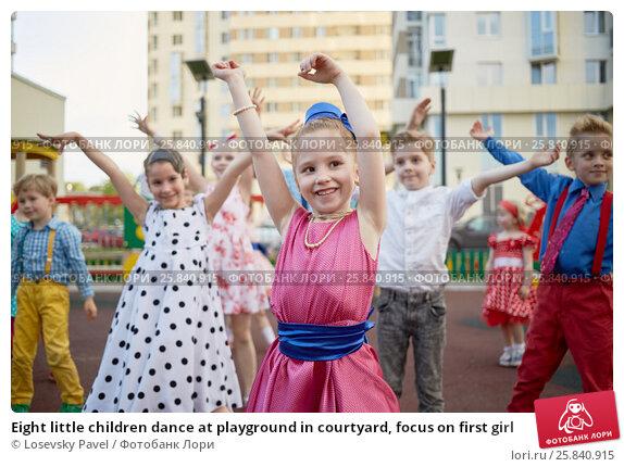 Купить «Eight little children dance at playground in courtyard, focus on first girl», фото № 25840915, снято 29 мая 2016 г. (c) Losevsky Pavel / Фотобанк Лори