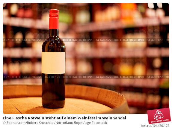 Eine Flasche Rotwein steht auf einem Weinfass im Weinhandel. Стоковое фото, фотограф Zoonar.com/Robert Kneschke / age Fotostock / Фотобанк Лори
