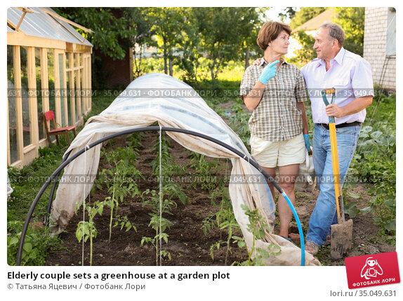 Elderly couple sets a greenhouse at a garden plot. Стоковое фото, фотограф Татьяна Яцевич / Фотобанк Лори