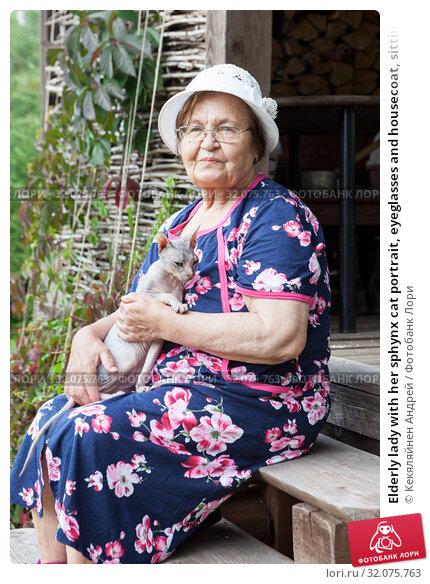 Elderly lady with her sphynx cat portrait, eyeglasses and housecoat, sitting on porch of timber house. Стоковое фото, фотограф Кекяляйнен Андрей / Фотобанк Лори