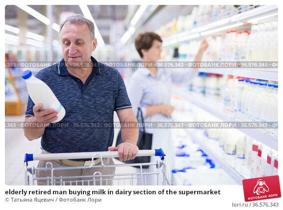 elderly retired man buying milk in dairy section of the supermarket. Стоковое фото, фотограф Татьяна Яцевич / Фотобанк Лори