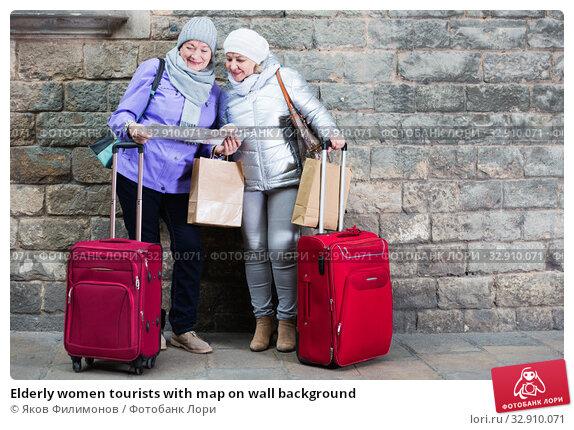Elderly women tourists with map on wall background. Стоковое фото, фотограф Яков Филимонов / Фотобанк Лори