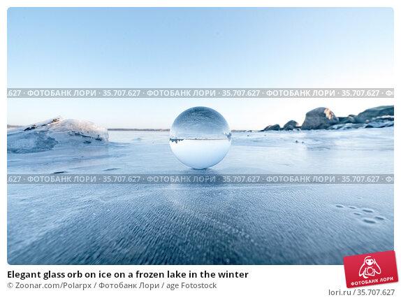 Elegant glass orb on ice on a frozen lake in the winter. Стоковое фото, фотограф Zoonar.com/Polarpx / age Fotostock / Фотобанк Лори
