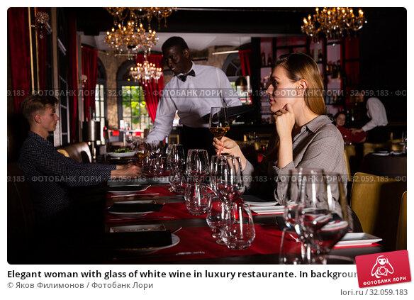 Elegant woman with glass of white wine in luxury restaurante. In background waiter serves guest. Стоковое фото, фотограф Яков Филимонов / Фотобанк Лори