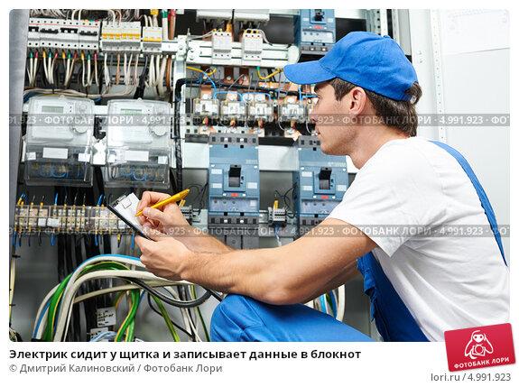 Купить «Электрик сидит у щитка и записывает данные в блокнот», фото № 4991923, снято 21 августа 2013 г. (c) Дмитрий Калиновский / Фотобанк Лори