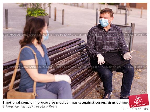 Купить «Emotional couple in protective medical masks against coronavirus communicate sittig on bench», фото № 33775343, снято 9 июля 2020 г. (c) Яков Филимонов / Фотобанк Лори