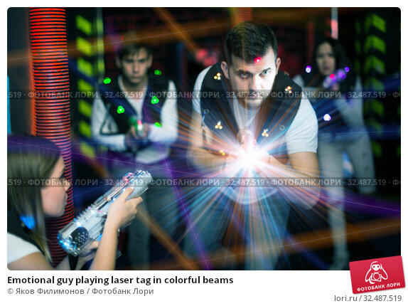 Купить «Emotional guy playing laser tag in colorful beams», фото № 32487519, снято 25 апреля 2018 г. (c) Яков Филимонов / Фотобанк Лори