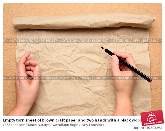 Empty torn sheet of brown craft paper and two hands with a black wooden... Стоковое фото, фотограф Zoonar.com/Danko Natalya / easy Fotostock / Фотобанк Лори