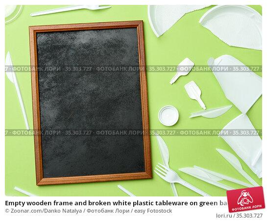Empty wooden frame and broken white plastic tableware on green background... Стоковое фото, фотограф Zoonar.com/Danko Natalya / easy Fotostock / Фотобанк Лори