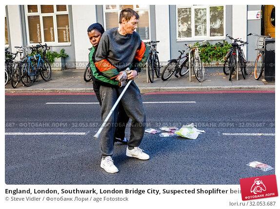 England, London, Southwark, London Bridge City, Suspected Shoplifter being Apprehended by Female Security Guard on Street. Стоковое фото, фотограф Steve Vidler / age Fotostock / Фотобанк Лори