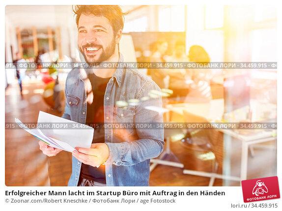 Erfolgreicher Mann lacht im Startup Büro mit Auftrag in den Händen. Стоковое фото, фотограф Zoonar.com/Robert Kneschke / age Fotostock / Фотобанк Лори