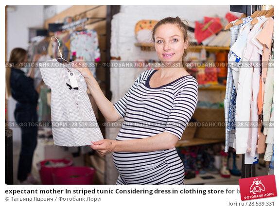 Купить «expectant mother In striped tunic Considering dress in clothing store for babies», фото № 28539331, снято 6 апреля 2017 г. (c) Татьяна Яцевич / Фотобанк Лори