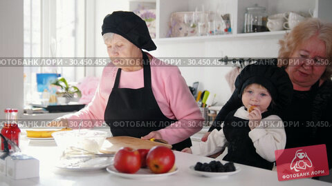 Family in the kitchen making desserts. An old woman about to cut the banana. Стоковое видео, видеограф Константин Шишкин / Фотобанк Лори