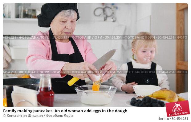Family making pancakes. An old woman add eggs in the dough. Стоковое фото, фотограф Константин Шишкин / Фотобанк Лори