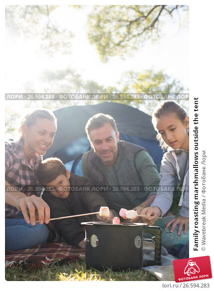Family roasting marshmallows outside the tent; фото ...