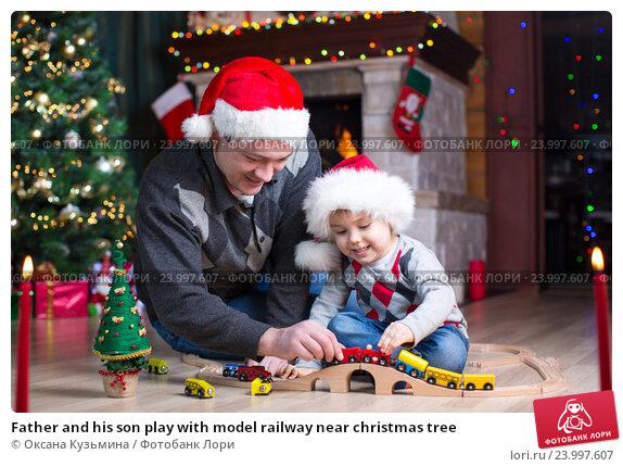 Купить «Father and his son play with model railway near christmas tree», фото № 23997607, снято 16 января 2016 г. (c) Оксана Кузьмина / Фотобанк Лори