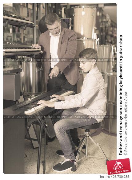 Купить «Father and teenage son examining keyboards in guitar shop», фото № 26730235, снято 29 марта 2017 г. (c) Яков Филимонов / Фотобанк Лори