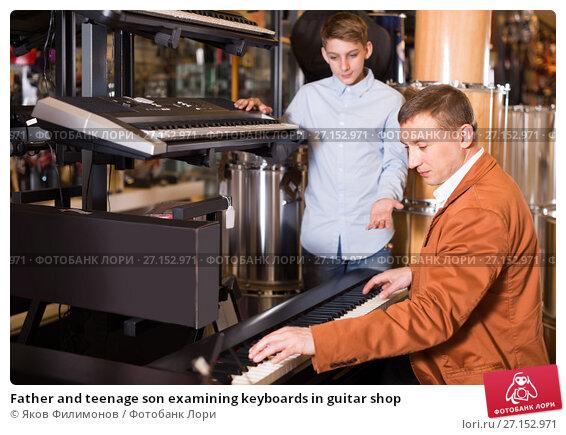 Купить «Father and teenage son examining keyboards in guitar shop», фото № 27152971, снято 29 марта 2017 г. (c) Яков Филимонов / Фотобанк Лори