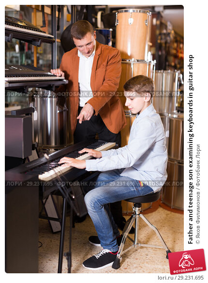 Купить «Father and teenage son examining keyboards in guitar shop», фото № 29231695, снято 29 марта 2017 г. (c) Яков Филимонов / Фотобанк Лори