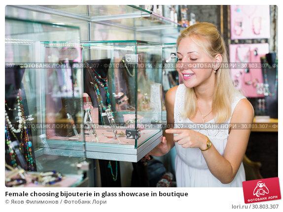 Купить «Female choosing bijouterie in glass showcase in boutique», фото № 30803307, снято 18 июня 2019 г. (c) Яков Филимонов / Фотобанк Лори