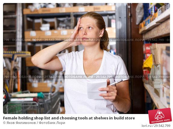 Купить «Female holding shop list and choosing tools at shelves in build store», фото № 29542799, снято 20 сентября 2018 г. (c) Яков Филимонов / Фотобанк Лори