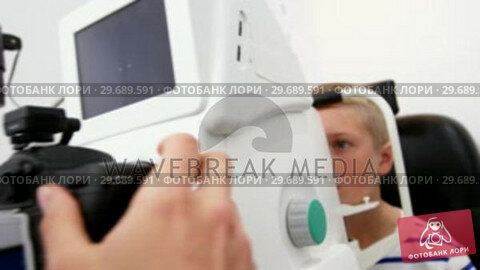 Купить «Female optometrist examining young patient on coreometry», видеоролик № 29689591, снято 20 июня 2016 г. (c) Wavebreak Media / Фотобанк Лори