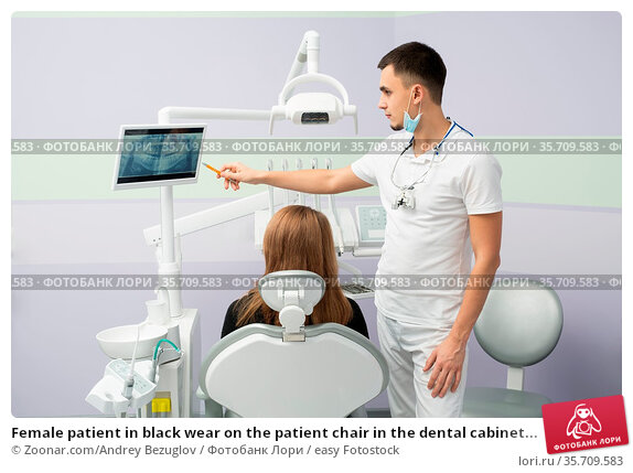 Female patient in black wear on the patient chair in the dental cabinet... Стоковое фото, фотограф Zoonar.com/Andrey Bezuglov / easy Fotostock / Фотобанк Лори