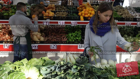 Female shopper picks onions at grocery store. Стоковое видео, видеограф Яков Филимонов / Фотобанк Лори