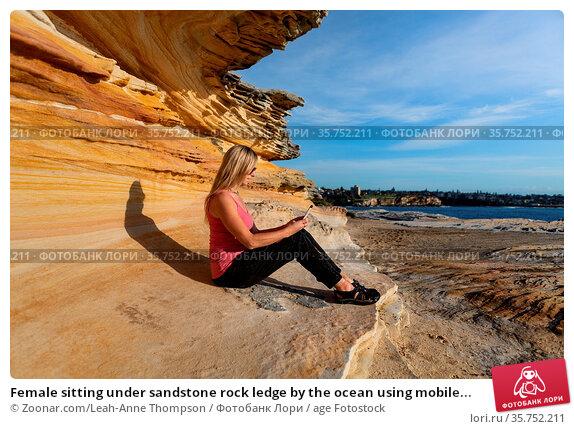 Female sitting under sandstone rock ledge by the ocean using mobile... Стоковое фото, фотограф Zoonar.com/Leah-Anne Thompson / age Fotostock / Фотобанк Лори