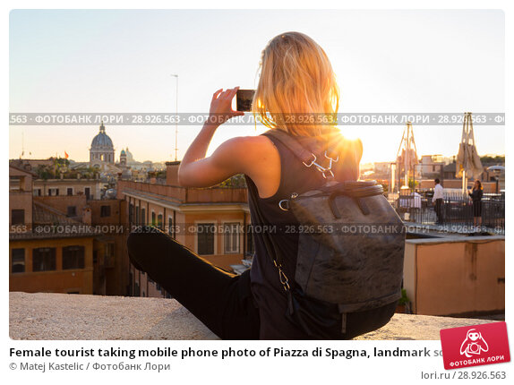 Купить «Female tourist taking mobile phone photo of Piazza di Spagna, landmark square with Spanish steps in Rome, Italy at sunset.», фото № 28926563, снято 21 августа 2018 г. (c) Matej Kastelic / Фотобанк Лори