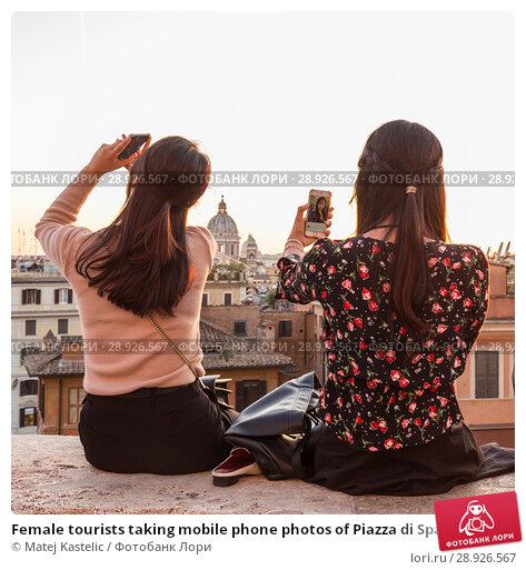 Купить «Female tourists taking mobile phone photos of Piazza di Spagna, landmark square with Spanish steps in Rome, Italy at sunset.», фото № 28926567, снято 21 августа 2018 г. (c) Matej Kastelic / Фотобанк Лори