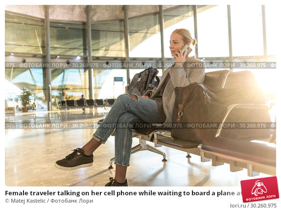 Купить «Female traveler talking on her cell phone while waiting to board a plane at departure gates at airport terminal.», фото № 30260975, снято 10 января 2019 г. (c) Matej Kastelic / Фотобанк Лори