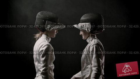 Купить «Fencing training - two young women walking off the dark and greeting each other before the duel», видеоролик № 32429267, снято 31 марта 2020 г. (c) Константин Шишкин / Фотобанк Лори