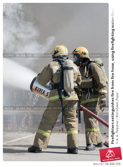 Firefighters extinguishes fire from fire hose, using firefighting water-foam barrel with air-mechanical foam (2019 год). Редакционное фото, фотограф А. А. Пирагис / Фотобанк Лори