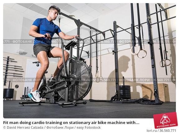 Fit man doing cardio training on stationary air bike machine with... Стоковое фото, фотограф David Herraez Calzada / easy Fotostock / Фотобанк Лори