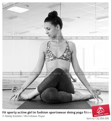 Fit sporty active girl in fashion sportswear doing yoga fitness exercise in yoga studio. Active urban lifestyle. Black and white image. Стоковое фото, фотограф Matej Kastelic / Фотобанк Лори