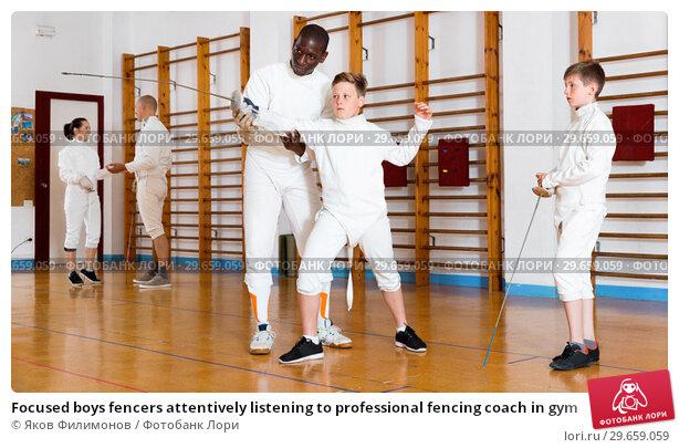 Купить «Focused boys fencers attentively listening to professional fencing coach in gym», фото № 29659059, снято 30 мая 2018 г. (c) Яков Филимонов / Фотобанк Лори