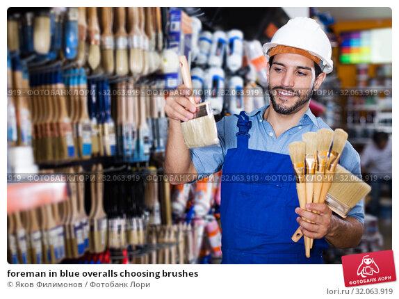 foreman in blue overalls choosing brushes. Стоковое фото, фотограф Яков Филимонов / Фотобанк Лори