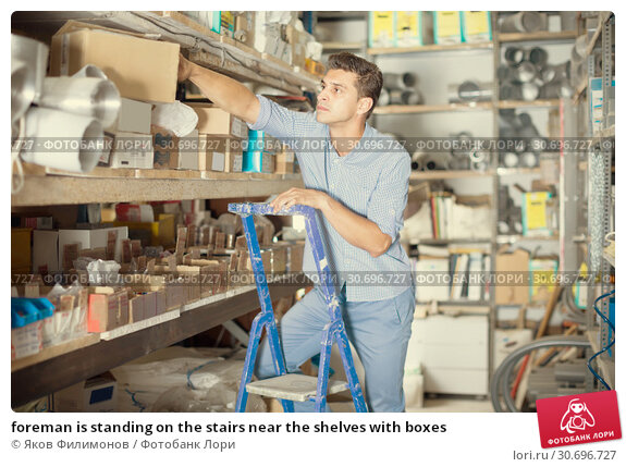 Купить «foreman is standing on the stairs near the shelves with boxes», фото № 30696727, снято 26 июля 2017 г. (c) Яков Филимонов / Фотобанк Лори
