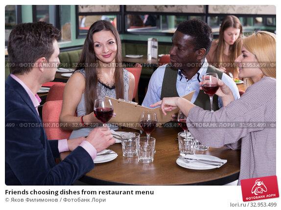 Friends choosing dishes from restaurant menu. Стоковое фото, фотограф Яков Филимонов / Фотобанк Лори