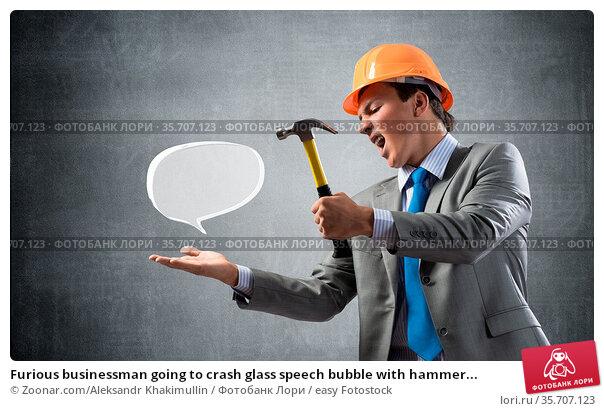 Furious businessman going to crash glass speech bubble with hammer... Стоковое фото, фотограф Zoonar.com/Aleksandr Khakimullin / easy Fotostock / Фотобанк Лори