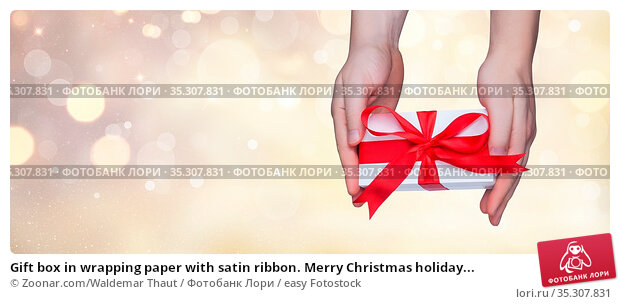 Gift box in wrapping paper with satin ribbon. Merry Christmas holiday... Стоковое фото, фотограф Zoonar.com/Waldemar Thaut / easy Fotostock / Фотобанк Лори