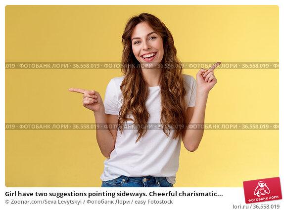 Girl have two suggestions pointing sideways. Cheerful charismatic... Стоковое фото, фотограф Zoonar.com/Seva Levytskyi / easy Fotostock / Фотобанк Лори