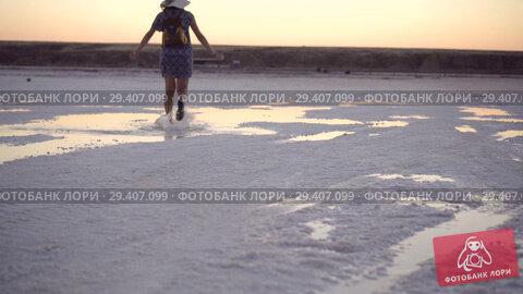 Купить «girl in green sandals splash jump through the puddles of salt lake at sunset time», видеоролик № 29407099, снято 3 ноября 2018 г. (c) Ирина Мойсеева / Фотобанк Лори