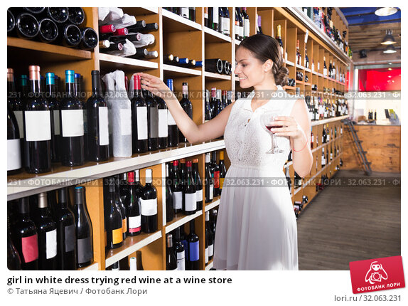 girl in white dress trying red wine at a wine store. Стоковое фото, фотограф Татьяна Яцевич / Фотобанк Лори