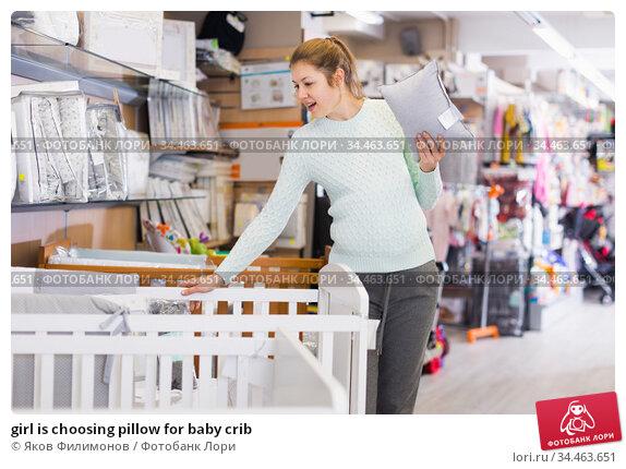 girl is choosing pillow for baby crib. Стоковое фото, фотограф Яков Филимонов / Фотобанк Лори