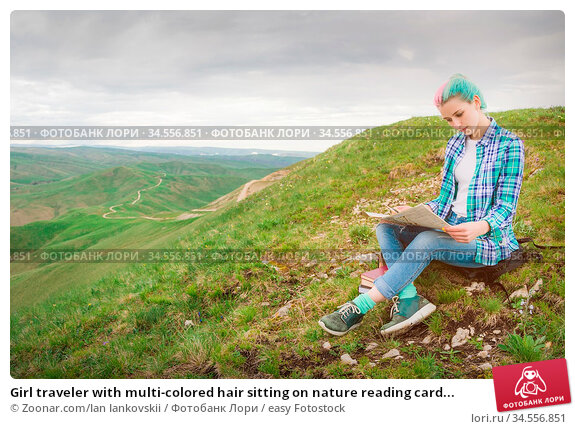 Girl traveler with multi-colored hair sitting on nature reading card... Стоковое фото, фотограф Zoonar.com/Ian Iankovskii / easy Fotostock / Фотобанк Лори