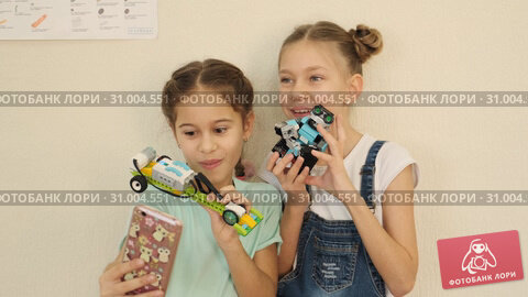 Girls have fun and laugh while doing selfie with robot cars at the class slow motion. Стоковое видео, видеограф Denis Mishchenko / Фотобанк Лори