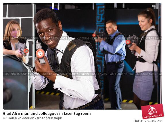 Купить «Glad Afro man and colleagues in laser tag room», фото № 32347235, снято 4 апреля 2019 г. (c) Яков Филимонов / Фотобанк Лори